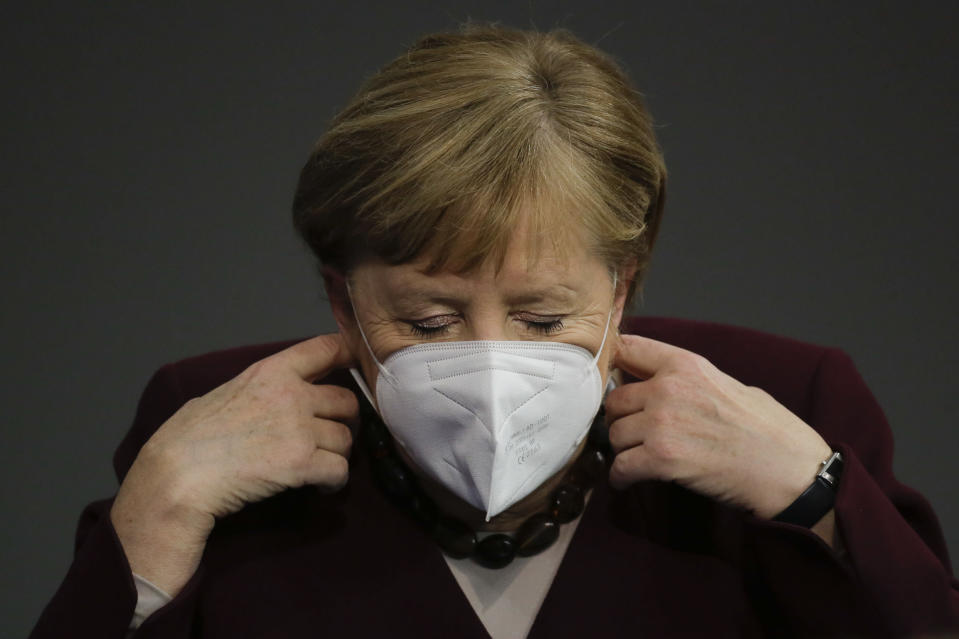 German Chancellor Angela Merkel adjusts her face mask as she arrives for a parliament session about German government's policies to combat the spread of the coronavirus and COVID-19 disease at the parliament Bundestag, in Berlin, Germany, Thursday, Nov. 26, 2020. Merkel and the country's 16 state governors have agreed to extend a partial shutdown well into December in an effort to further reduce the rate of coronavirus infections ahead of the Christmas period. (AP Photo/Markus Schreiber)