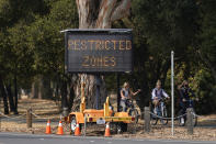 Bicyclists ride past a road sign advising restricted zones around the Stanford University campus in Stanford, Calif., Wednesday, Sept. 2, 2020. (AP Photo/Jeff Chiu)