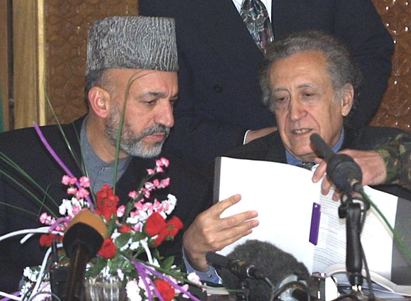 FILE - This is a Friday, Jan. 4, 2002 file photo of Afghan interim Prime Minister Hamid Karzai, left, and U.N. Special Representative to Afghanistan Lakhdar Brahimi, examine the agreement which establishes the role of International Security Assistance Force for Afghanistan, at a gathering in Kabul. Lakhdar Brahimi has seen faces like these before, barely able to remain in the same room, much less speak to each other. Lebanese, Afghans, Iraqis, now Syrians. Even, two decades ago, Algerians like himself. For days now, the veteran U.N. mediator has presided over peace talks intended to lead the way out of Syria's civil war. He brought President Bashar Assad's government and the opposition face to face for the first time on Saturday, Jan. 25, 2014, while still ensuring that they don't have to enter by the same door or address each other directly. He is 80. He is patient. (AP Photo/Brennan Linsley. File)