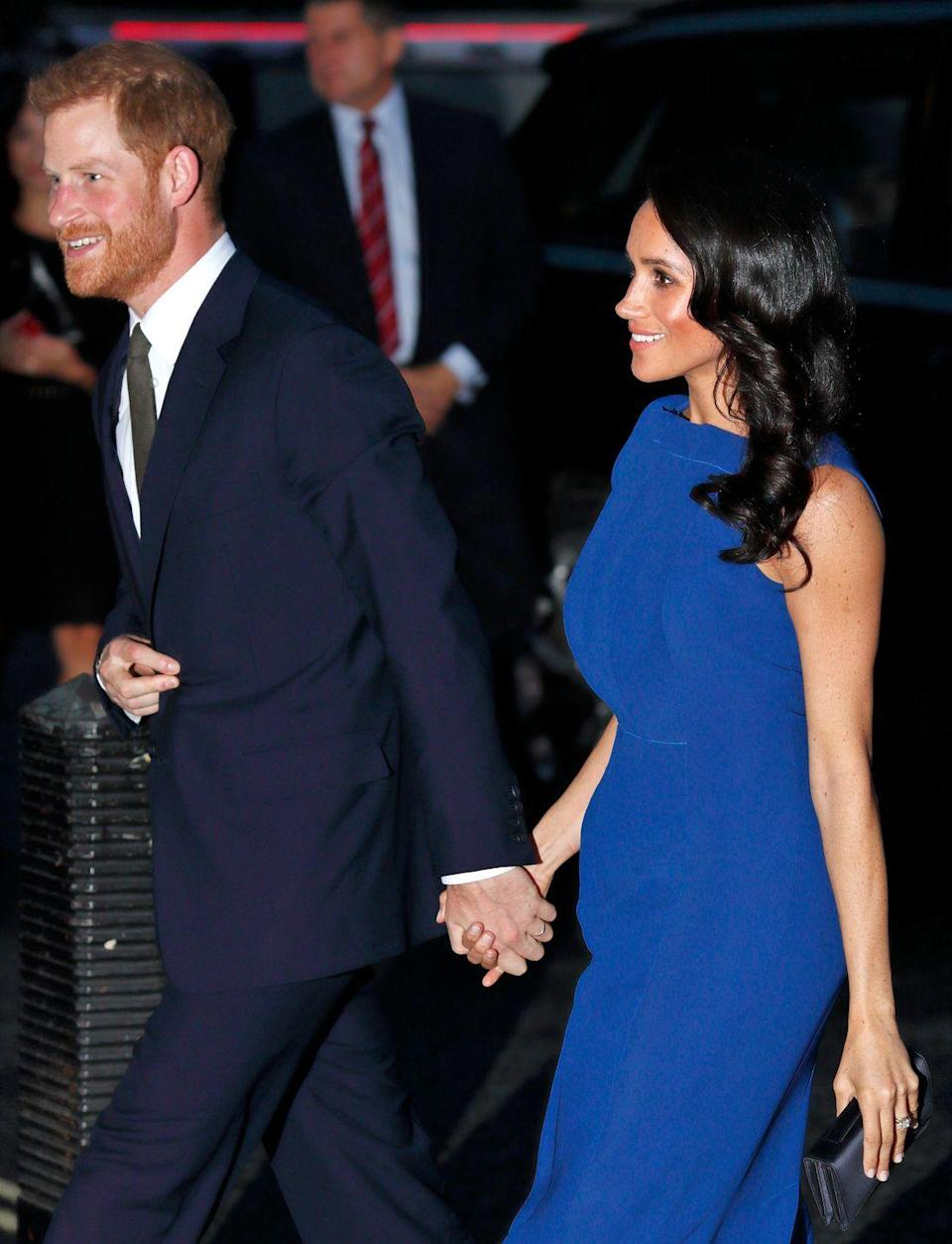 """<p>The Duke & Duchess Of Sussex looked at ease as they held hands at the'100 Days Of Peace' Commemorative Concert in Westminster. Wearing a blue <a href=""""https://www.elle.com/uk/fashion/celebrity-style/news/a42368/jason-wu-dress-meghan-markle/"""" rel=""""nofollow noopener"""" target=""""_blank"""" data-ylk=""""slk:Jason Wu dress"""" class=""""link rapid-noclick-resp"""">Jason Wu dress</a> for the occasion, Meghan beamed with pride as she walked alongside her husband, September 2018</p>"""