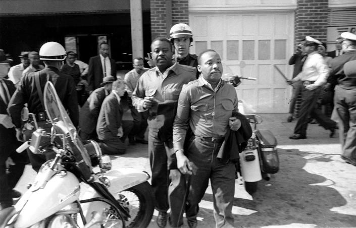 <p>Rev. Ralph Abernathy, left, and Rev. Martin Luther King Jr., right are taken by a policeman as they led a line of demonstrators into the business section of Birmingham, Ala., on April 12, 1963. (AP Photo) </p>