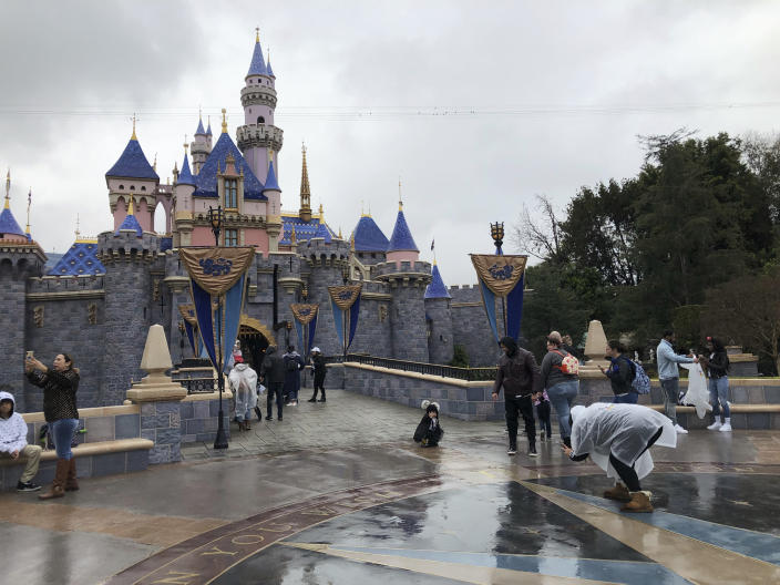 Visitors take photos at Disneyland in Anaheim, Calif., Friday, March 13, 2020. Disneyland is closing its doors for the rest of the month, shuttering one of California's best-known attractions as the state hurries to stop the spread of the coronavirus. (AP Photo/Amy Taxin)