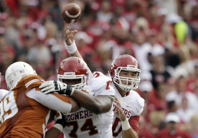 Oklahoma quarterback Blake Bell (10) passes as offensive linesman Adam Shead (74) blocks Texas defensive tackle Desmond Jackson (99) during the first half of an NCAA college football game at the Cotton Bowl Saturday, Oct. 12, 2013, in Dallas. (AP Photo/LM Otero)