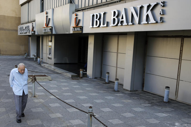 A man passes by a closed bank in Beirut, Lebanon, Tuesday, Nov. 12, 2019. Lebanon's banking association says banks will stay closed due to a strike by employees, as country's financial crisis worsens. (AP Photo/Bilal Hussein)