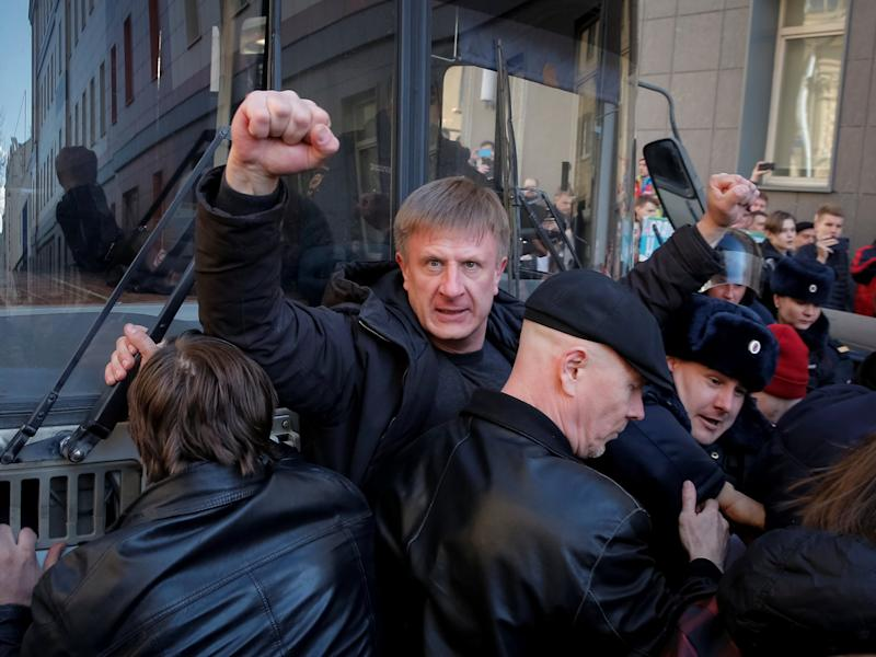 An opposition supporter gestures as he blocks a police van transporting detained anti-corruption campaigner and opposition figure Alexei Navalny during a rally in Moscow, Russia, March 26, 2017.