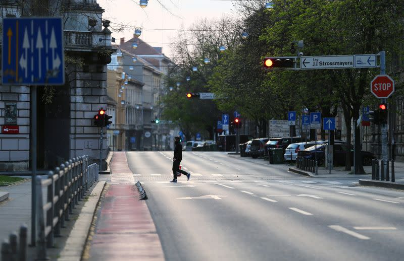 A man crossing a street as Croatia is stepping up measures to fight the coronavirus disease (COVID-19) outbreak