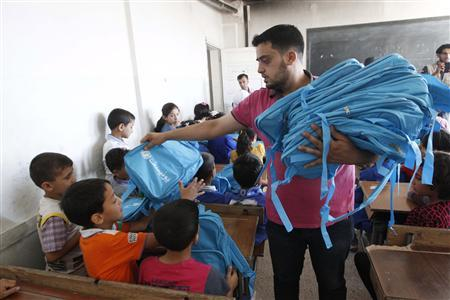 A man distributes bags donated from UNICEF to young students in Raqqa