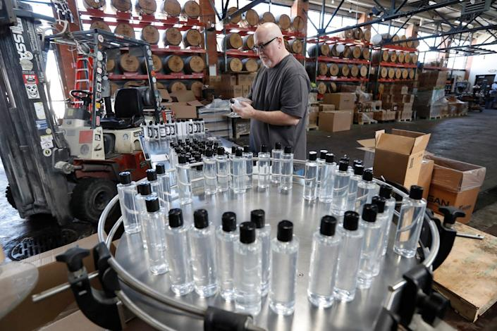 A Two James Spirits employee applies labels to bottles of hand sanitizer produced at the distillery on April 3 in Detroit.