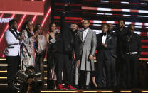 FILE - This Jan. 26, 2020 file photo shows DJ Khaled, center left, and John Legend, center right, and members of Nipsey Hussle's family accepting the award for best rap/sung performance at the 62nd annual Grammy Awards in Los Angeles. Hussle, 33, was shot and killed outside his Los Angeles clothing store on March 31, 2019. A year after Hussle's death, his popularity and influence are as strong as ever. He won two posthumous Grammys in January, he remains a favorite of his hip-hop peers and his death has reshaped his hometown of Los Angeles in some unexpected ways. (Photo by Matt Sayles/Invision/AP, File)