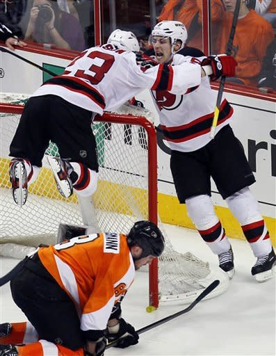 New Jersey Devils' Zach Parise, right, and David Clarkson, laying on the net, who scored what would be the game-winning goal celebrate during the third period in Game 2 of an NHL hockey Stanley Cup second-round playoff series with the Philadelphia Flyers, Tuesday, May 1, 2012, in Philadelphia. Flyers, Nick Grossmann kneels down in the crease. The Devils won 4-1 tying the best of seven series at 1-1.(AP Photo/Tom Mihalek)