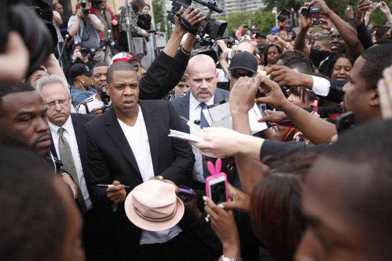 """Entertainer Shawn """"Jay-Z"""" Carter signs a fans hat after a news conference at the Philadelphia Museum of Art, Monday, May 14, 2012, in Philadelphia. The rapper announced plans for a two-day music festival in Philadelphia's at Fairmount Park, featuring nearly 30 acts """"that embody the American spirit"""" on Labor Day weekend, Sept. 1 and Sept. 2, 2012. (AP Photo/Matt Rourke)"""