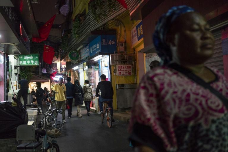 """People walk in Guangzhou's """"Little Africa"""" district in March 2018 (AFP Photo/FRED DUFOUR)"""