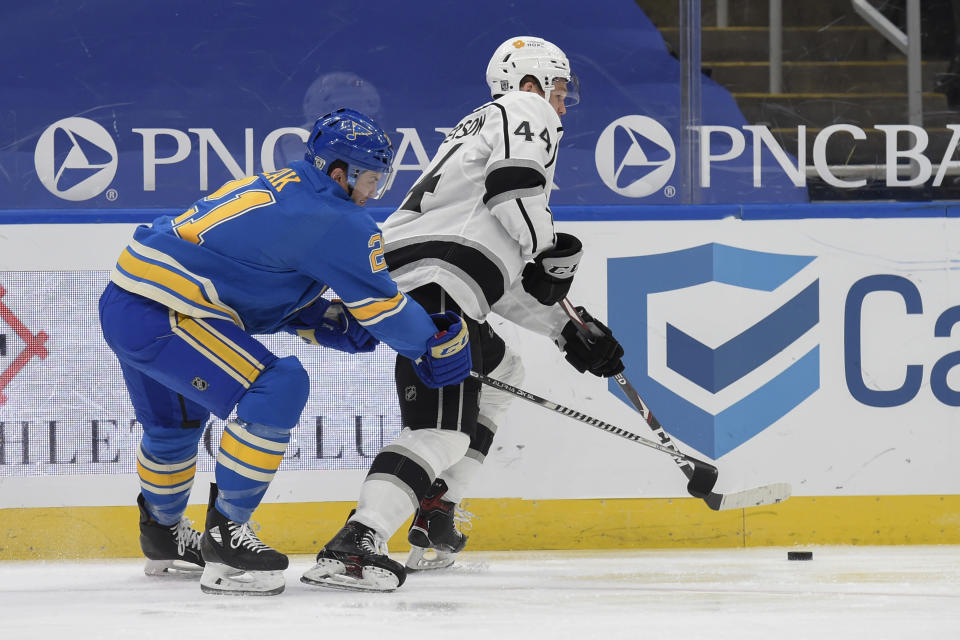 St. Louis Blues' Tyler Bozak (21) battles Los Angeles Kings' Mikey Anderson (44) for the puck during the second period of an NHL hockey game Saturday, Jan. 23, 2021, in St. Louis. (AP Photo/Joe Puetz)