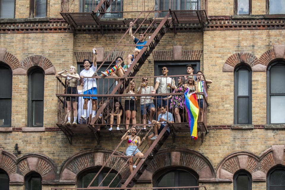 People watch the Queer Liberation March from their fire escape on Sunday, June 27, 2021, in New York. (AP Photo/Brittainy Newman)