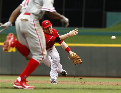 Cincinnati Reds third baseman Todd Frazier, right, throws out Philadelphia Phillies' Juan Pierre, left, at first base in the third inning in the first inning during a baseball game, Monday, Sept. 3, 2012, in Cincinnati. (AP Photo/David Kohl)