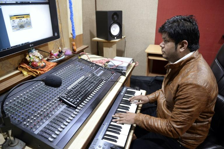 Indian music director Amarjit Singh plays a keyboard during a recording session with Indian singer Ginni Mahi at a studio in Jalandhar