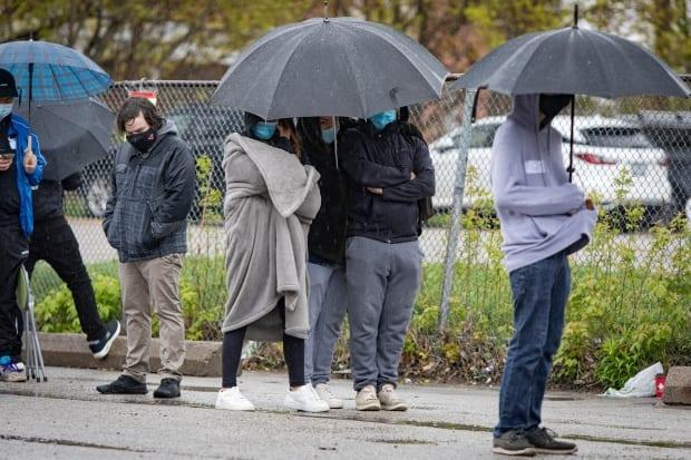 People living in neighbourhoods deemed to be at a higher risk of COVID-19 transmission line up in the rain outside Downsview Arena, in Toronto's northwest, on Apr. 29, 2021. (Evan Mitsui/CBC - image credit)