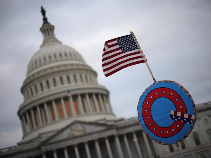 Supporters of Donald Trump fly a US flag with a symbol from the group QAnon as they gather outside the US Capitol on 6 January 2021 in Washington, DC ((Getty Images))
