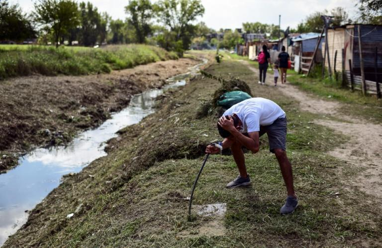 A man washes his hair next to a water-filled ditch in the 28 de Octubre slum in La Matanza