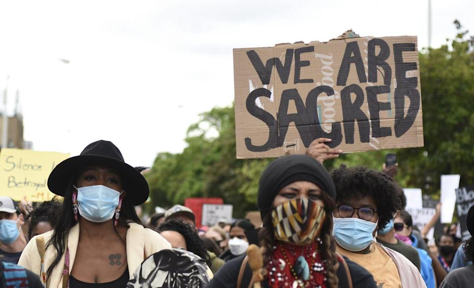 <p>A young woman holds up a sign expressing the sacredness of BIPOC lives and bodies. </p>