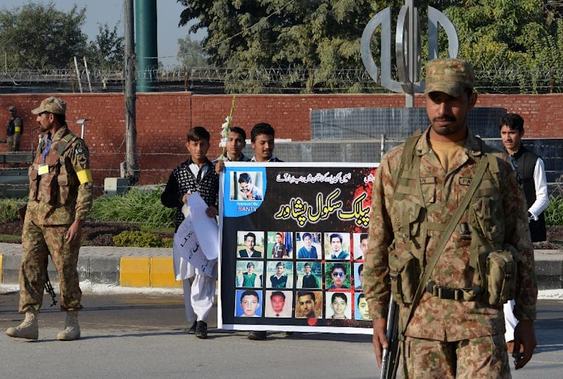 Pakistani students carry a banner bearing images of victims of the Peshawar school massacre as army troops cordon off a street leading to the Army Public School due to mark the first anniversary of the attack, on December 16, 2015 (AFP Photo/A Majeed)
