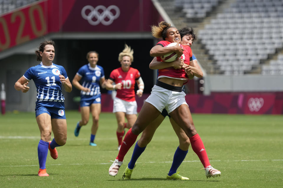 CORRECTS TO BRITAIN NOT BRAZIL - Britain's Celia Quansah gets lifted by Russian Olympic Committee's Baizat Khamidova, in their women's rugby sevens match at the 2020 Summer Olympics, Thursday, July 29, 2021 in Tokyo, Japan. (AP Photo/Shuji Kajiyama)