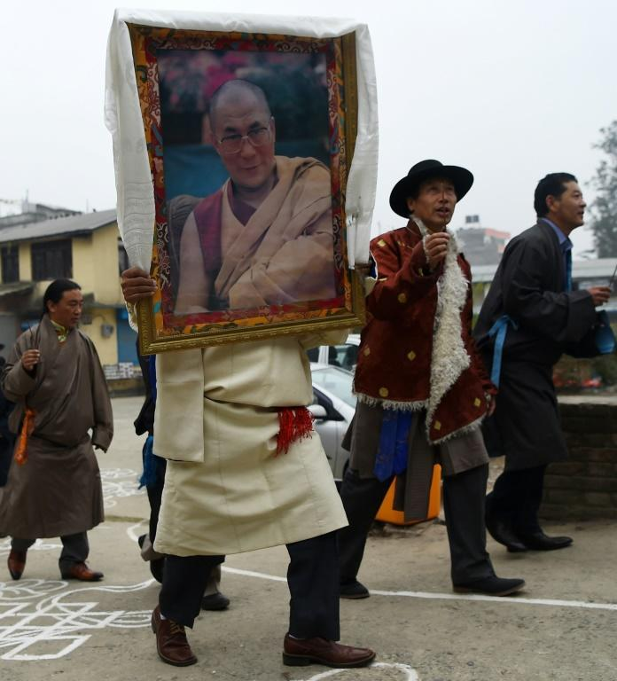 A Tibetan-in-exile carries a photograph of the Dalai Lama during celebrations marking the Lunar New Year in Kathmandu in February 2018