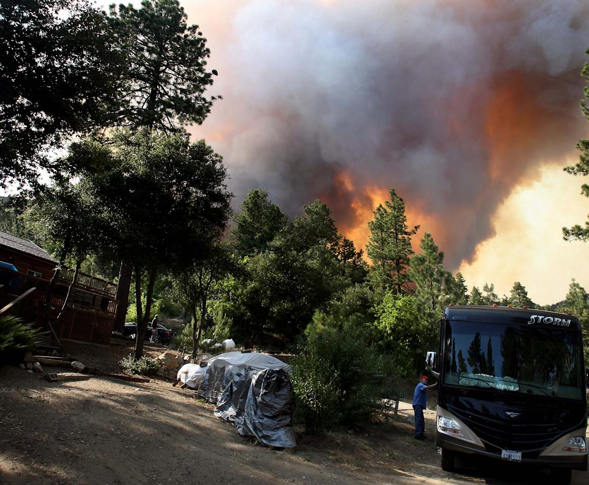 Doug Dowalter gets in his motor home to evacuate from his home on Morris Ranch Rd from the Mountain Fire near Lake Hemet on Tuesday July 16, 2013. The 14,200 acre forest fire near Idyllwild Calif., has caused Idyllwild and adjacent communities east of Highway 243 to issue mandatory evacuations for hundreds of homes Wednesday. (AP Photo/The Press-Enterprise, Frank Bellino)