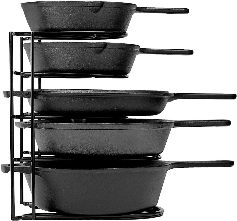 """This canaccommodate all of your pans — including heavy cast-iron skillets and Dutch ovens.<br /><br /><strong>Promising review:</strong>""""I have owned multilevel pan storage rack in the past, however this is by far the most solid and well made one I have ever seen. Most are just wire hardly thicker than a coat hanger but this one is over a quarter-inch of solid steel with an enameled coating to protect your pans.<strong>The spacing between each level is wider than average to accommodate almost any frying pan I've seen.</strong>And unlike any similar product I've seen it can be fastened down to the cabinet bottom so the whole thing doesn't move or tip over when you remove a pan. And the fasteners are included."""" --<a href=""""https://amzn.to/3h22ygi"""" target=""""_blank"""" rel=""""noopener noreferrer"""">PhotoGraphics</a><br /><br /><strong>Get it from Amazon for <a href=""""https://amzn.to/3h7ZqzE"""" target=""""_blank"""" rel=""""noopener noreferrer"""">$21.99+</a> (available in six colors).</strong>"""