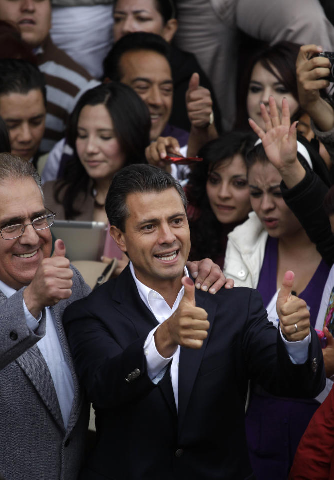 Enrique Pena Nieto, presidential candidate for the Revolutionary Institutional Party (PRI) shows his ink-stained thumbs after he cast his vote during general elections in Atlacomulco, Mexico, Sunday, July 1, 2012. Mexico PRI presidential candidate Pena Nieto leads with about 40 percent of the vote, according to first exit polls. (AP Photo/Dario Lopez-Mills)