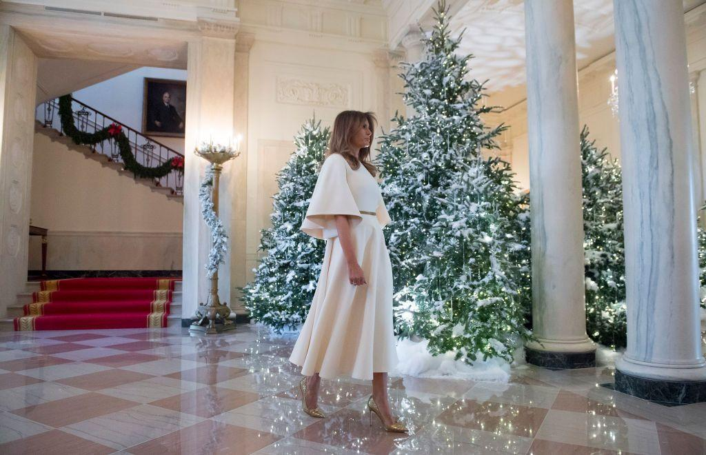 "<p>FLOTUS wore a cream Dior dress with a gold belt and gold stilettos to walk through the <a href=""https://www.townandcountrymag.com/society/g13943774/white-house-christmas-decorations/"" target=""_blank"">White House Christmas decorations</a>.</p>"