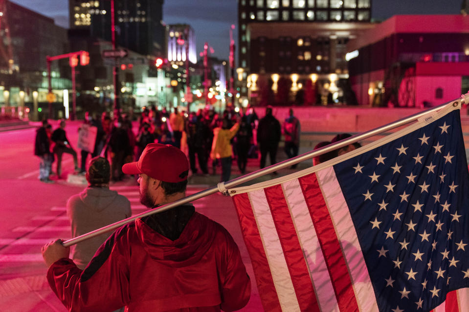 A Trump supporter demonstrating against the election results holds an American flag as counter protestors stand across the street outside the central counting board at the tcf Center in Detroit, Thursday, Nov. 5, 2020. (AP Photo/David Goldman)
