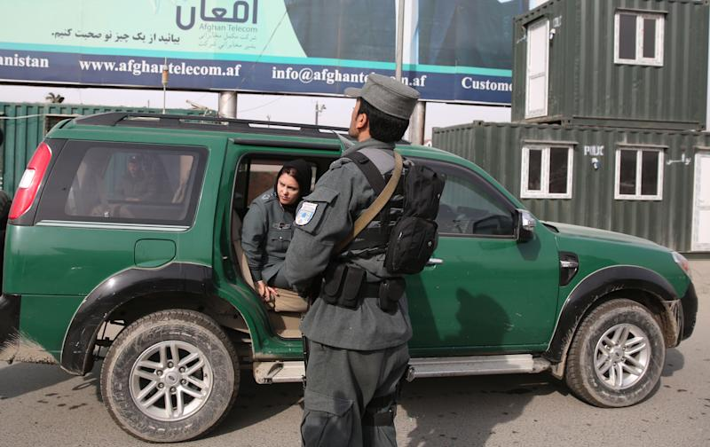 Afghanistan's first-ever female district police chief, Col. Jamila Bayaz, 50, left, gets off a police vehicle to review a check post in Kabul, Afghanistan, Thursday, Jan. 16, 2014. Afghanistan's first-ever female district police chief drew stares on Thursday as she drove and walked around the center of the city, reviewing check points and some of the important business and administrative facilities she is tasked with protecting. (AP Photo/Massoud Hossaini)