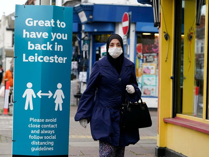 A woman wearing a PPE mask walks past social distance advisory signs in Leicester's North Evington neighbourhood on June 29, 2020 in Leicester, England: Getty