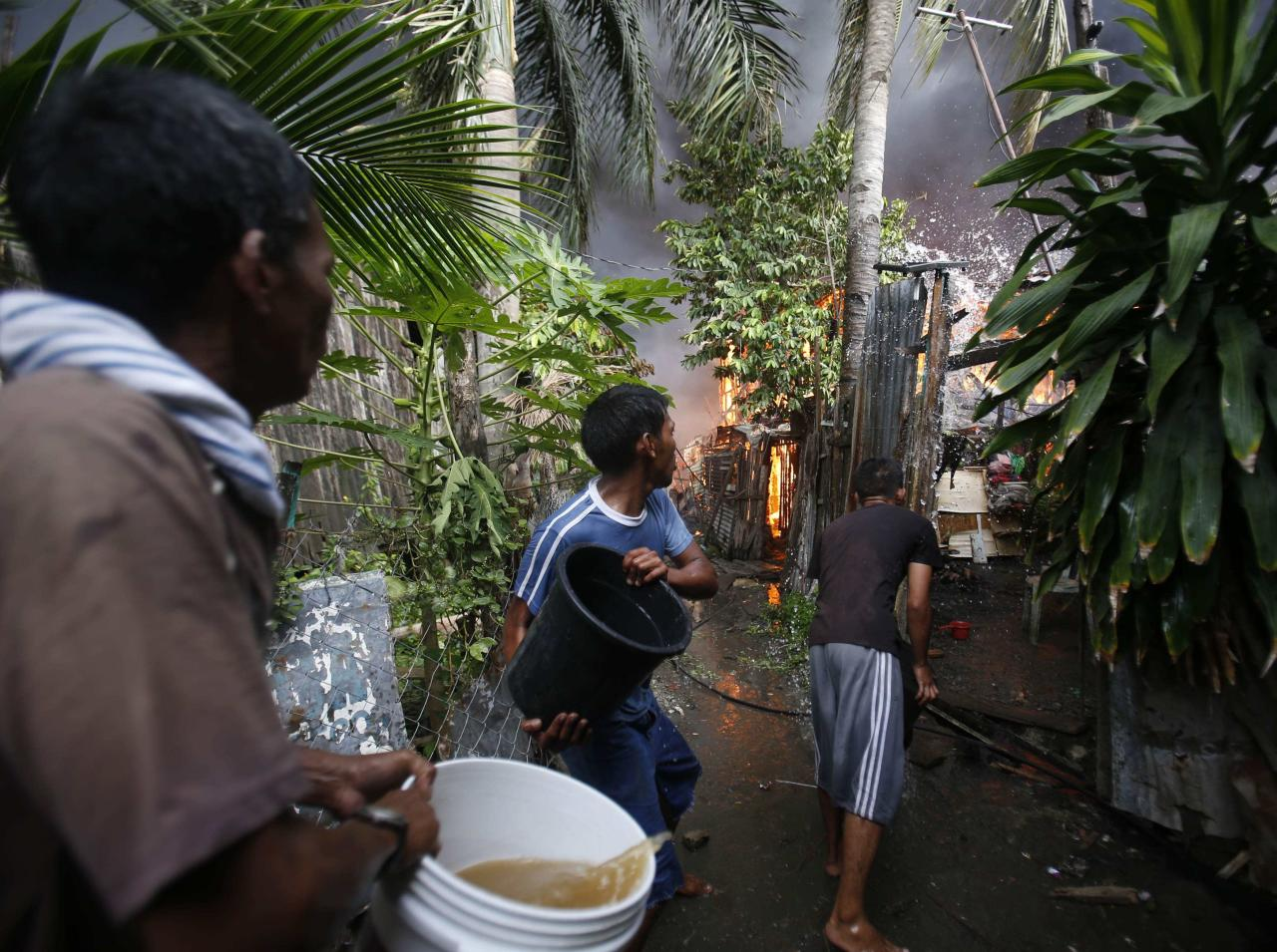 Residents attempt to put out the fire from their burning houses after a firefight between security forces and Muslim rebels from the MNLF in Zamboanga city, in southern Philippines