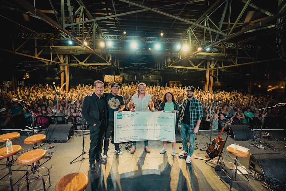 Morgan Wallen poses with 5,000 mock-check at benefit for flood victims at Marathon Music Works in Nashville - Credit: David Lehr