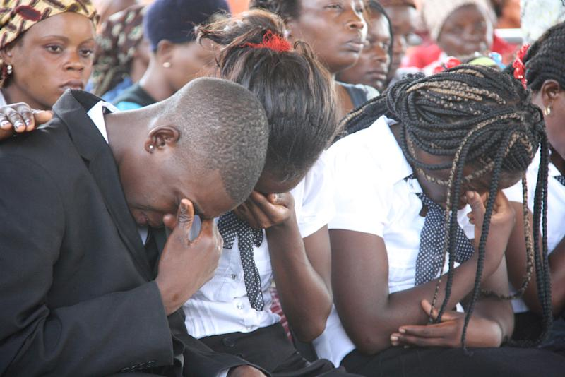 CORRECTING SPELLING OF MOZAMBIQUE - Unidentified mourners attend the funeral of Mozambican taxi driver Mido Macia in Matola, Mozambique, Saturday, March 9, 2013. Macia died of injuries received when police allegedly tied him to the back of a police vehicle and dragged him through the streets of Daveyton, in neighbouring South Africa. (AP Photo/Ferhat Momade)