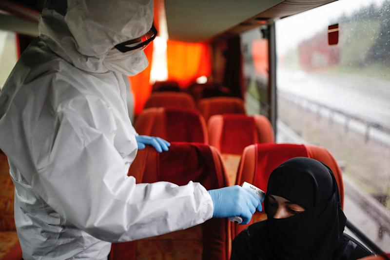 A health official measures the body temperature of a passenger on a bus at a check point in Istanbul, on March 29.