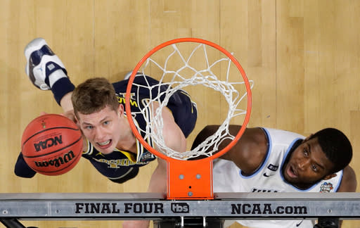 Michigan forward Moritz Wagner, left, drives to the basket over Villanova forward Eric Paschall during the first half in the championship game of the Final Four NCAA college basketball tournament, Monday, April 2, 2018, in San Antonio. (AP Photo/David J. Phillip)