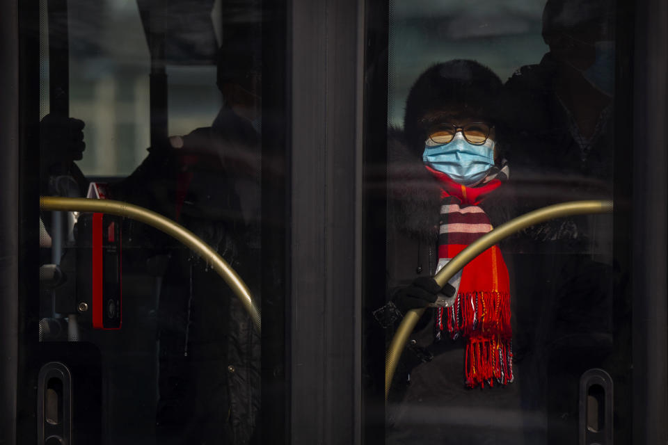 A woman wearing a face mask to protect against the spread of the coronavirus rides a public bus in Beijing, Wednesday, Jan. 20, 2021. China is now dealing with coronavirus outbreaks across its frigid northeast, prompting additional lockdowns and travel bans. (AP Photo/Mark Schiefelbein)