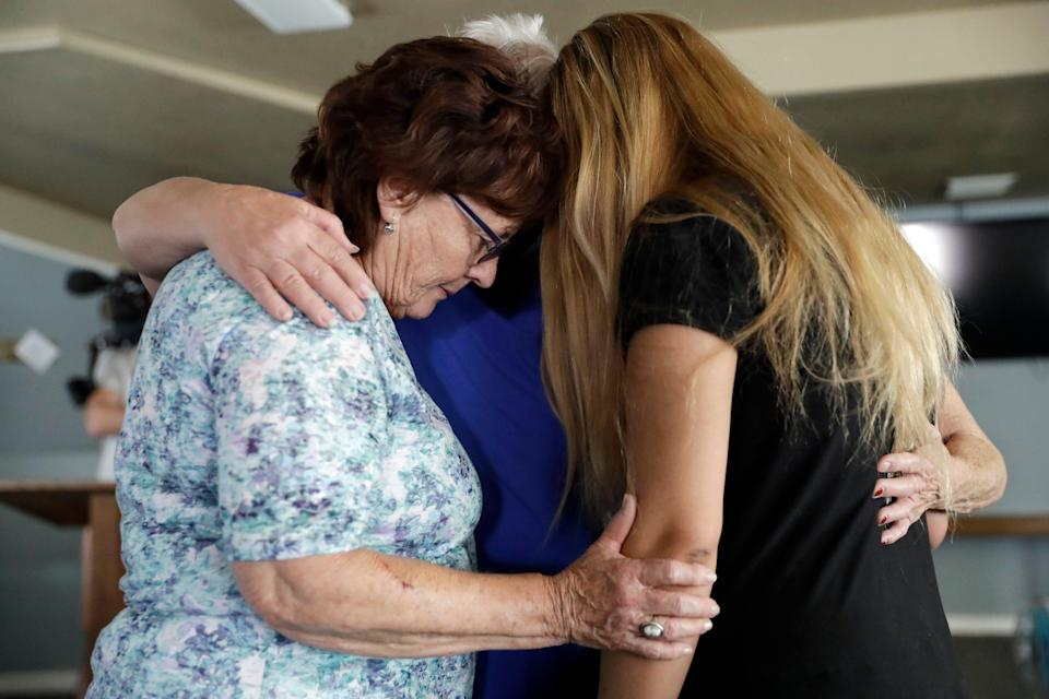 Alexandria Johnson, at right, whose home was damaged by an earthquake, prays with fellow congregants including Sara Smith, left, in the aftermath of an earthquake at the Christian Fellowship of Trona, July 7, 2019, in Trona, Calif.