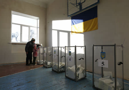 A man casts a ballot as a girl stands next to him during a parliamentary election at a school gym in the village of Semyonovka near Slaviansk, eastern Ukraine, October 26, 2014. REUTERS/Vasily Fedosenko