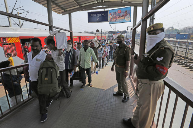 """Policemen stand guard as daily wage laborers, returning from Mumbai amid Coronavirus concerns arrive at a railway station in Prayagraj, India, Sunday, March 22, 2020. India is observing a 14-hour """"people's curfew"""" called by Prime Minister Narendra Modi in order to stem the rising coronavirus caseload in the country of 1.3 billion. For most people, the new coronavirus causes only mild or moderate symptoms. For some it can cause more severe illness. (AP Photo/Rajesh Kumar Singh)"""