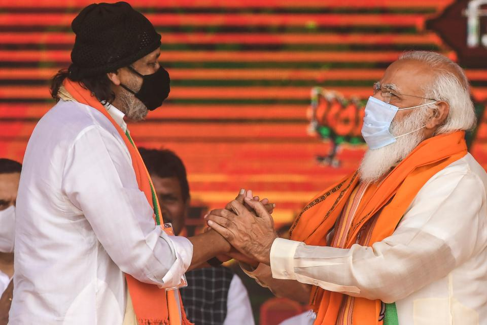 Bollywood actor Mithun Chakraborty (R), a former Trinamool Rajya Sabha member, greets India's Prime Minster Narendra Modi during a mass rally ahead of the state legislative assembly elections at the Brigade Parade ground in Kolkata on March 7, 2021. (Photo by Dibyangshu SARKAR / AFP) (Photo by DIBYANGSHU SARKAR/AFP via Getty Images)
