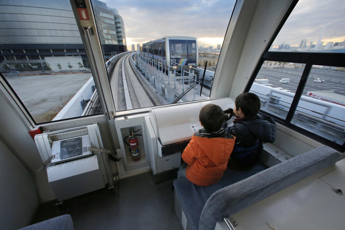 In this Jan. 10, 2013, photo, children ride in the very front seats of Tokyo's Yurikamome Line that runs without any drivers or conductors along Tokyo Bay. Katsuya Hagane, the manager in charge of operations at New Transit Yurikamome, which employees just 60 regular employees, says the automated systems reduce the number of staff needed. (AP Photo/Shizuo Kambayashi)