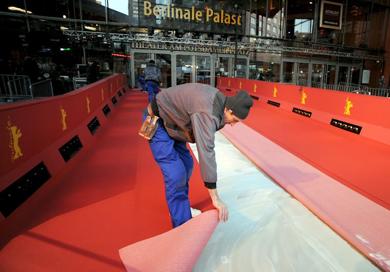 Workers lay the red carpet for the start of the Berlin International Film Festival at Potsdamer Platz in Berlin, Germany, Wednesday Feb. 5, 2014. The festival will run from Feb. 6 until Feb. 16, 2014. (AP Photo/dpa,Britta Pedersen)