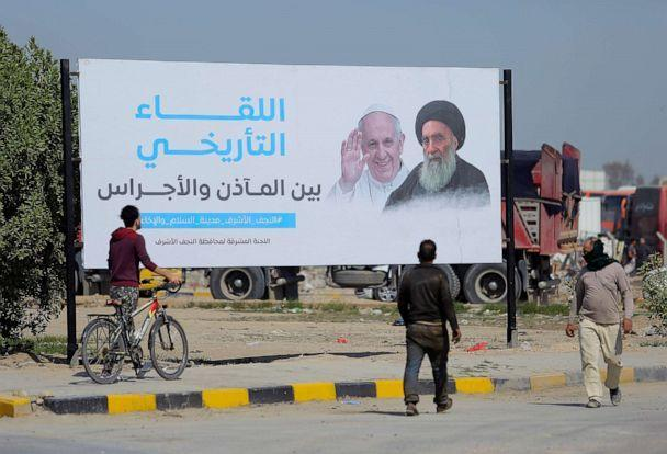 PHOTO: Iraqis walk by a poster announcing the upcoming visit of the Pope Francis and a meeting with a revered Shiite Muslim leader, Grand Ayatollah Ali al-Sistani, right, in Najaf, Iraq, March 3, 2021. (Anmar Khalil/AP)