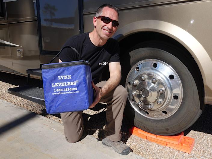 Marc holding Tri-Lynx Levelers that come in a ten pack with a handy storage bag while kneeling next to the RV with the blocks on a tire