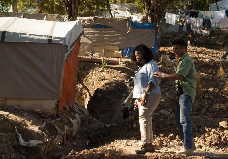 Oprah Winfrey, left, stands with actor Sean Penn in a camp for people displaced by the devastating 2010 earthquake in what was once a golf club in Port-au-Prince, Haiti, Monday, Dec. 12, 2011.  Winfrey is visiting the settlement camp run by Penn and his aid group J/P HRO.  (AP Photo/Lionel Lafortune)