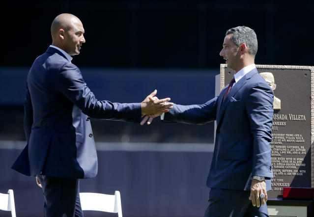 File-This Aug. 22, 2015, file photo shows, former New York Yankees catcher Jorge Posada, right, greeting retired Yankee shortstop Derek Jeter during a ceremony in which Posada's jersey number, 20, was retired before a baseball game against the Cleveland Indians. A person with knowledge of the negotiations says Posada has agreed to team up with Jeter again, this time in the front office of the Miami Marlins. The person says Posada will work as a special adviser to Jeter, his longtime New York Yankees teammate and now Marlins CEO. The person spoke to The Associated Press Tuesday, Feb. 12, 2019, on condition of anonymity because the hiring has not been formally announced. (AP Photo/Julie Jacobson,File)